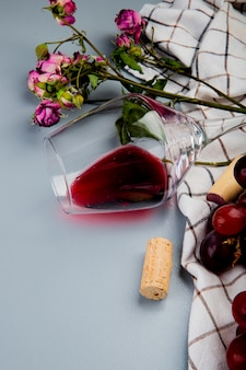 Side view of lying glass of red wine with flowers and corks on cloth on white