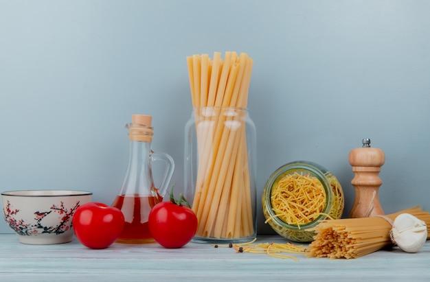 Vista laterale dei maccheroni come vermicelli degli spaghetti dei bucatini con il burro dell'aglio del pomodoro su superficie di legno e su fondo blu