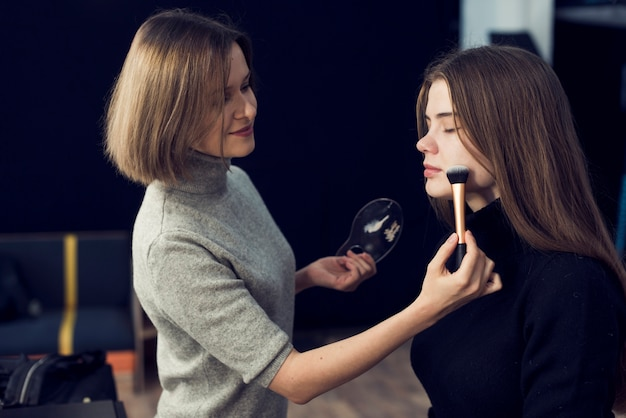 Side view makeup artist applying powder on model