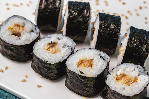 Вид сбоку рис маки, завернутый в водоросли с жареной рыбой и кунжутом на столе