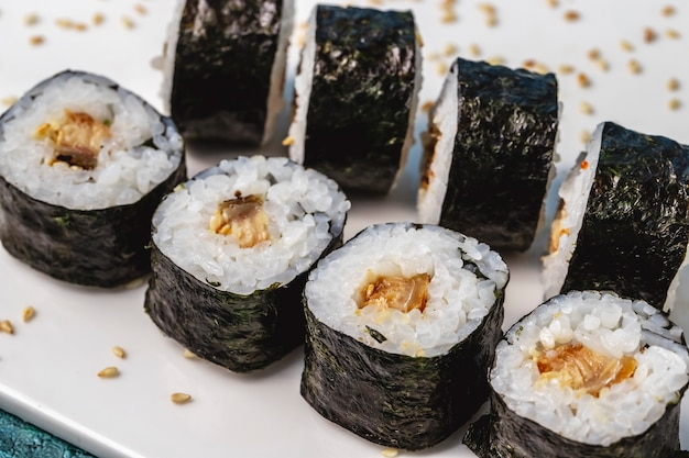 Side view maki rice wrapped in seaweed with fried fish and sesame seeds on the table