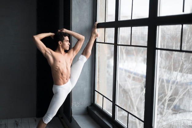 Side view of male ballet dancer stretching next to window