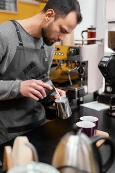 Vista laterale del barista maschio che prepara caffè