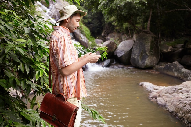 Side view of male biologist with leather bag at field work conducting water analysis standing at mountain river and taking pictures using digital tablet with waterfall and rocks