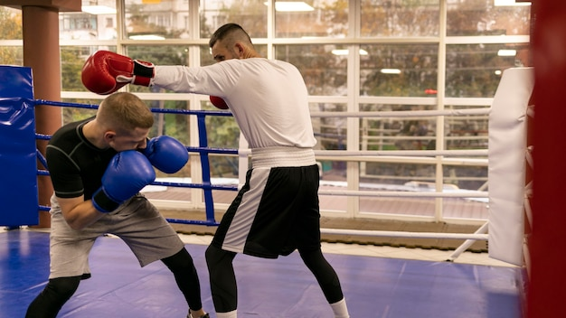 Side view of male boxer practicing with trainer