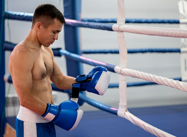 Side view of male boxer next to ring