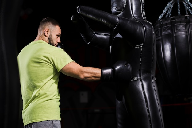 Side view of male boxer in t-shirt with punching bag
