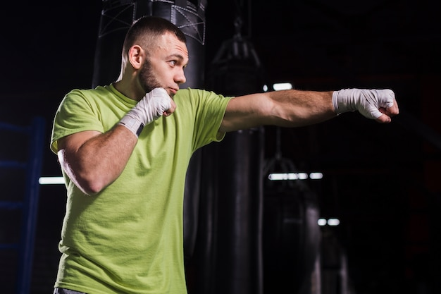 Side view of male boxer throwing punches in the gym