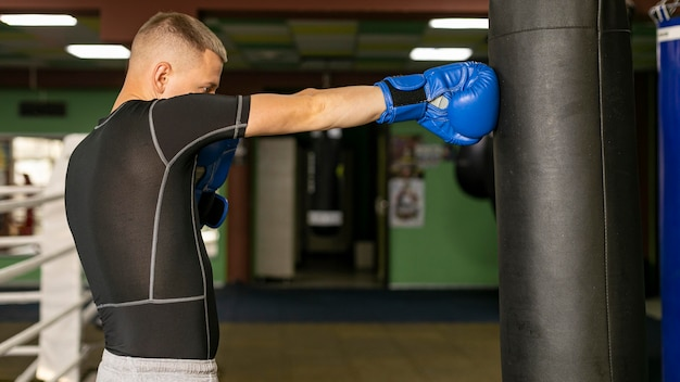 Side view of male boxer with gloves training