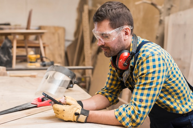 Side view of a male carpenter using mobile phone in the workshop