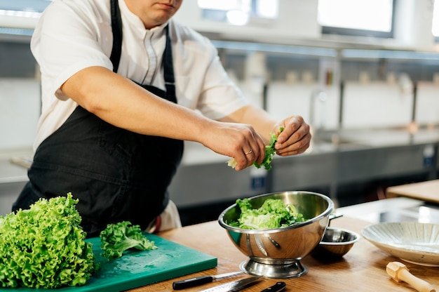 Side view of male chef tearing salad in bowl