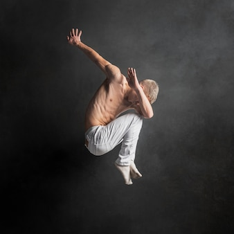 Side view of male dancer posing in mid-air