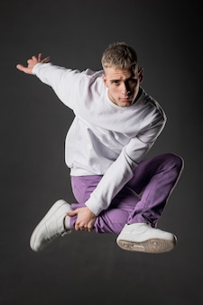 Side view of male dancer in purple jeans posing in mid-air