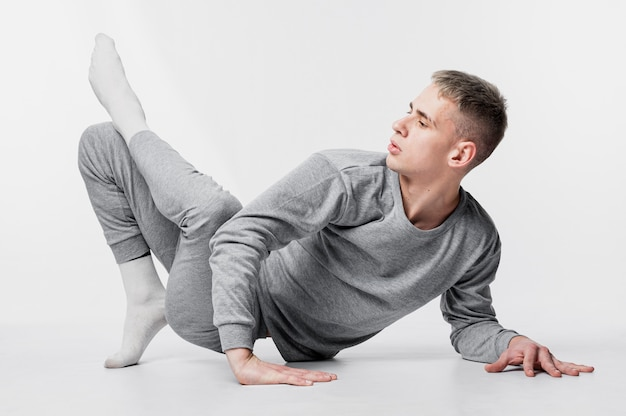 Side view of male dancer in socks and tracksuit posing while dancing