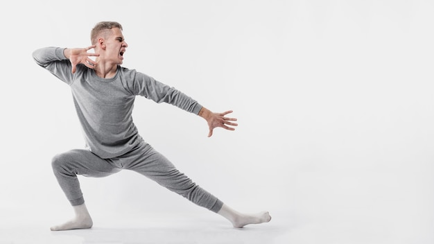 Side view of male dancer in tracksuit and socks posing