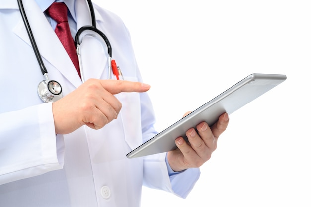 A side view of a male doctor using a tablet on a white background.