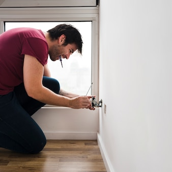 Side view of male electrician carrying tester in mouth while fixing plug socket at home