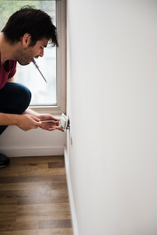 Side view of male electrician fixing plug on white wall