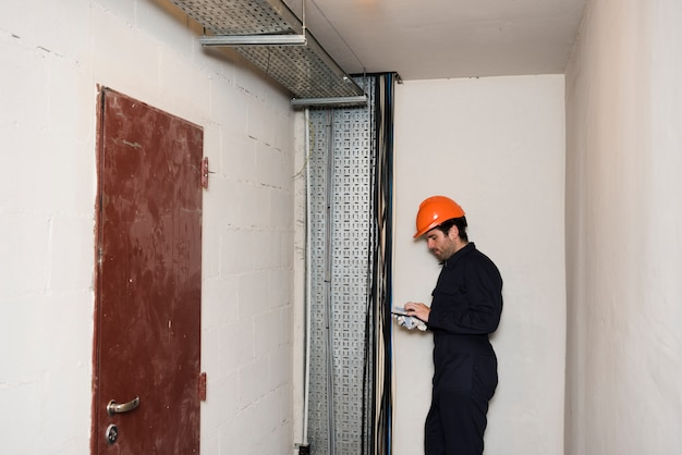 Side view of male electrician using mobile phone at work