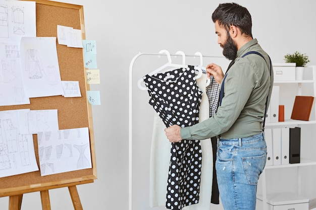 Side view of male fashion designer checking dress in atelier
