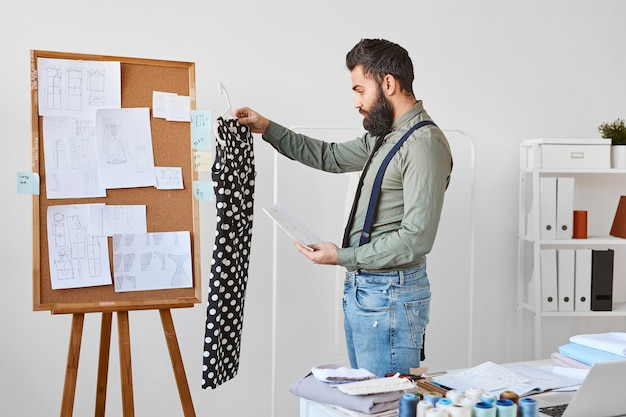 Side view of male fashion designer working with dress in atelier