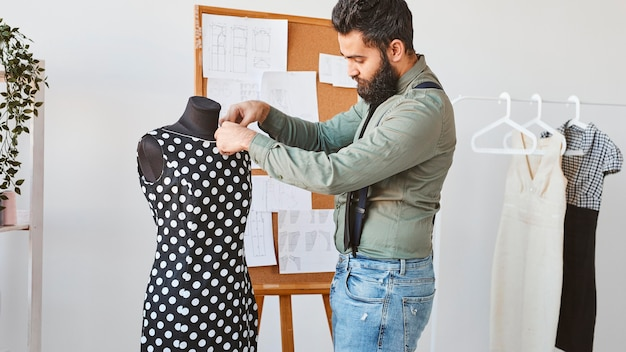 Side view of male fashion designer working with dress form in atelier