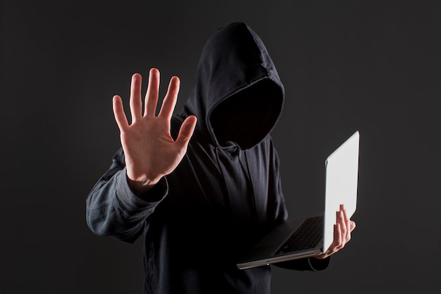 Side view of male hacker holding laptop and putting hand up as stop