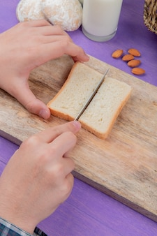Side view of male hands cutting bread slice on cutting board with almonds gingerbreads milk on purple surface