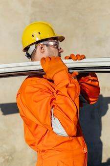Vista laterale del lavoratore maschio con elmetto che trasportano acciaio
