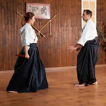 Vista laterale dell'istruttore di arti marziali maschio e tirocinante femminile nella sala pratica