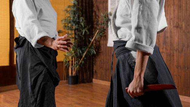 Vista laterale dell'istruttore di arti marziali maschio nella sala pratica e tirocinante femminile
