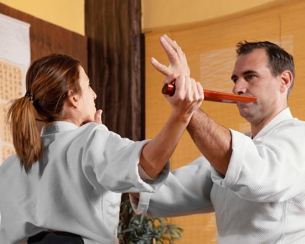 Vista laterale dell'istruttore di arti marziali maschio nella sala pratica con tirocinante femminile