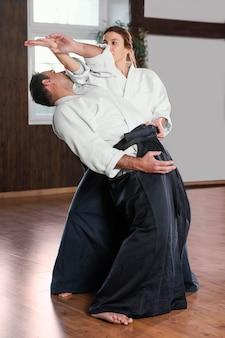 Vista laterale dell'istruttore di arti marziali maschio che si allena nella sala pratica con tirocinante femminile
