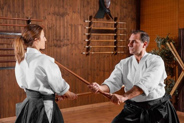 Vista laterale della formazione di istruttori di arti marziali maschili nella sala pratica con giovane tirocinante femminile