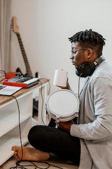 Vista laterale del musicista maschio a casa che suona la batteria e si mescola con il laptop