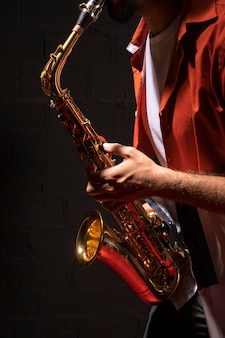 Side view of male musician playing saxophone