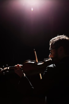 Side view of male musician playing the violin with copy space