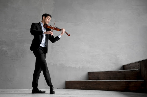 Side view of male musician playing violin