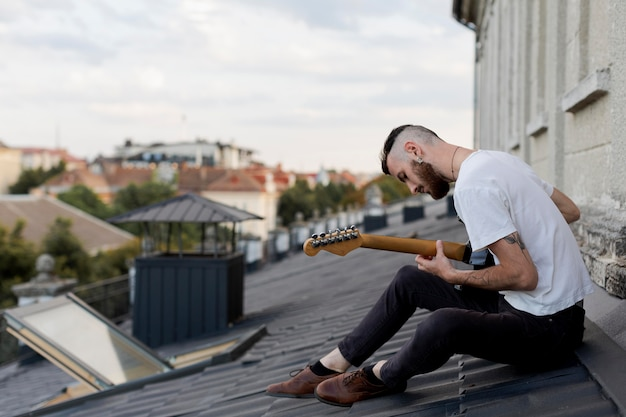 Side view of male musician on roof top playing electric guitar