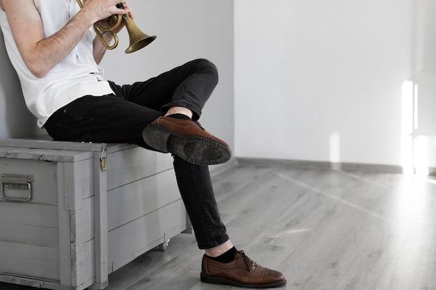 Vista laterale del musicista maschio con cornetta e copia spazio