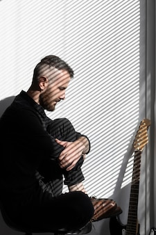 Side view of male musician with electric guitar next to window