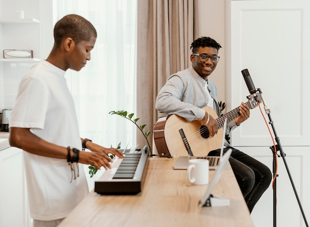 Vista laterale di musicisti maschi a casa a suonare la chitarra e la tastiera elettrica