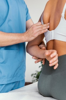 Side view of male osteopathic therapist checking female patient's scapula bone