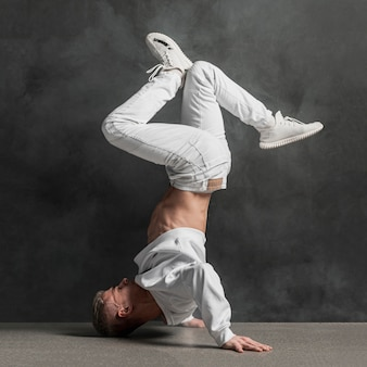 Side view of male performer in jeans and sneakers holding legs up