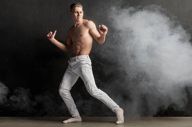 Side view of male performer posing in jeans with smoke and copy space