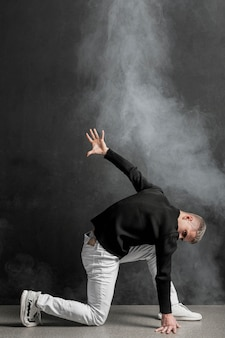 Side view of male performer posing in jeans with smoke