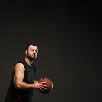 Side view of male player holding basketball with copy space