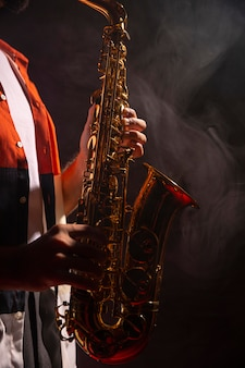 Vista laterale del maschio che suona il sassofono sotto i riflettori