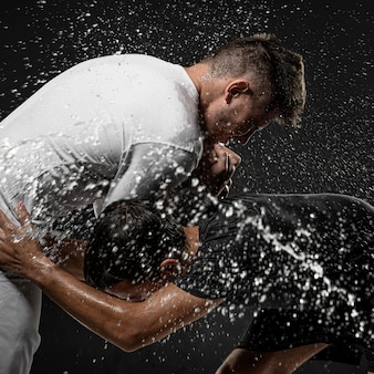 Side view of male rugby players with ball and water splashes