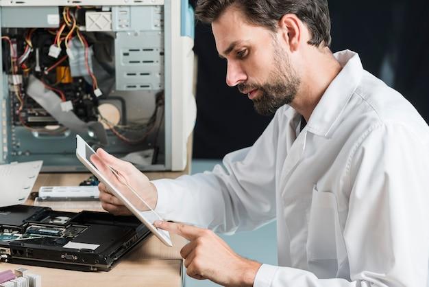 Vista laterale di un tecnico maschile utilizzando la tavoletta digitale